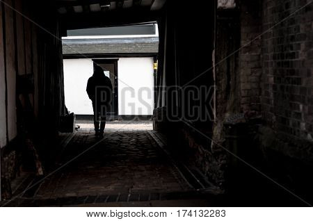 Figure of a man in an alley in the shadows