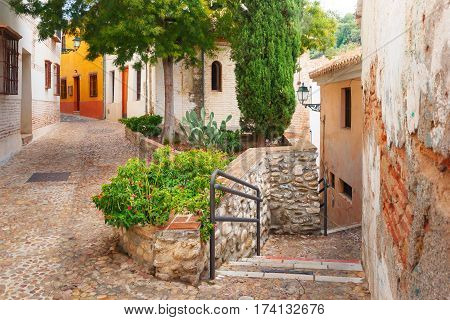Scenic alley with traditional Spanish white houses in the old town area of Albaicin, Granada, Andalusia, Spain