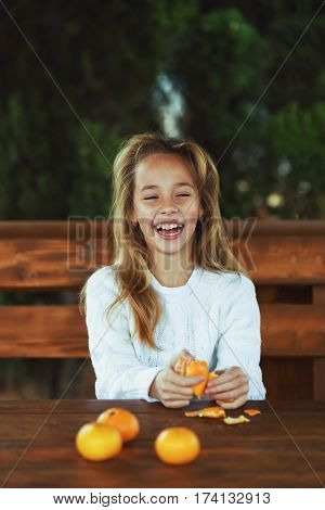 a happy preteen girl with a tangerine