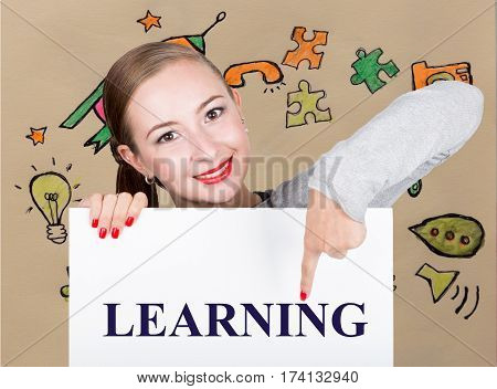 Young woman holding whiteboard with writing word: learning. Technology, internet, business and marketing