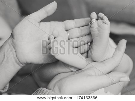 newborn's foot in the mother hand with wedding rings on finger