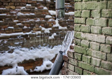 Broken frozen downspout tube with ice inside