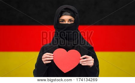 love, charity, valentines day, immigration and people concept - muslim woman in hijab holding red heart over german flag background