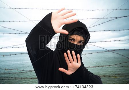 crime, imprisonment, violence, refugee and people concept - muslim woman in hijab making protective gesture over sea and barb wire background