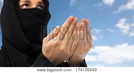 religion, faith, islam and people concept - close up of praying muslim woman in hijab over blue sky and clouds background