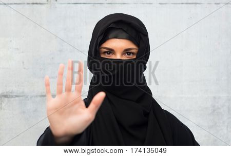 gesture, religious prohibition and people concept - muslim woman in hijab showing stop sign over gray concrete wall background