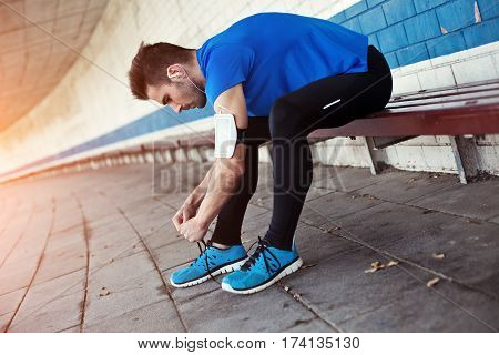 handsome athlete tying shoelaces and preparing for running