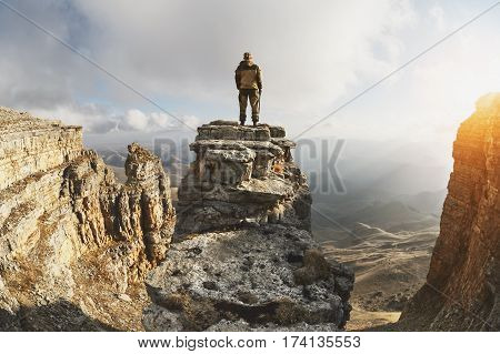 A young man stands on a rock surrounded by cliffs, located above the clouds in a great location, on a background of clouds, valleys, fields, mountains and sunset