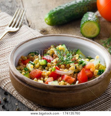 Delicious Israeli couscous Ptitim with vegetables on a table. Healthy vegetarian food for the meal. Traditional Moroccan cuisine.