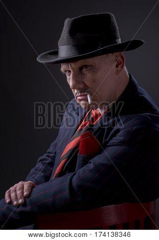 Mature Jazz man/gangster  smoking a cigarette on a black background