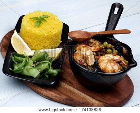 Arrangement of Delicious Seafood Curry with Saffron Rice and Cucumber Salad on Serving Board with Wooden Spoon closeup on Wooden background