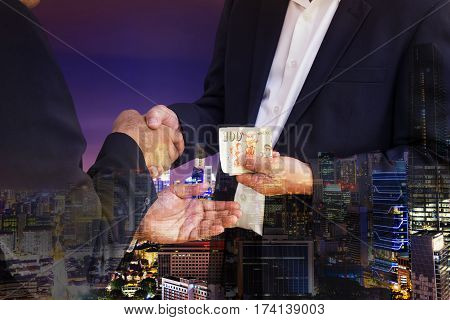 double exposure of businessman are shaking hand and getting money and cityscape in corruption concept - can use to display or montage on product