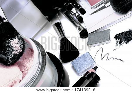 Arrangement of Make up Products with Eyeshadow Moisturizer Mascara Blush Face Powder and Personal Accessory closeup on White background