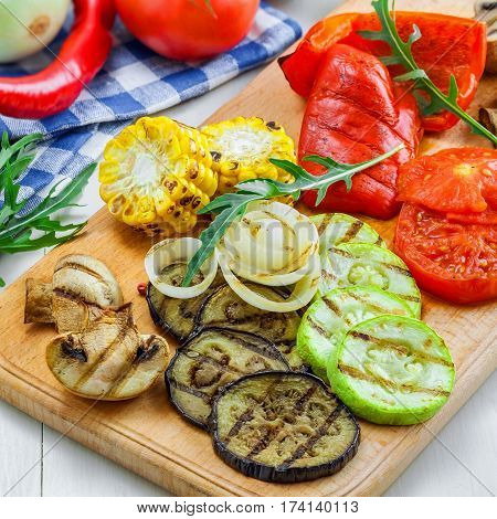 Grilled vegetables: tomato corn eggplant mushroom bell pepper marrow and onion. Delicious healthy food and ingredients on a table.