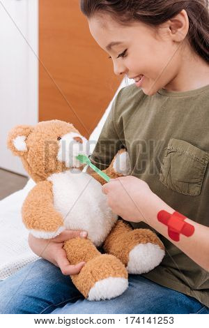 side view of smiling girl playing doctor and patient with teddy bear