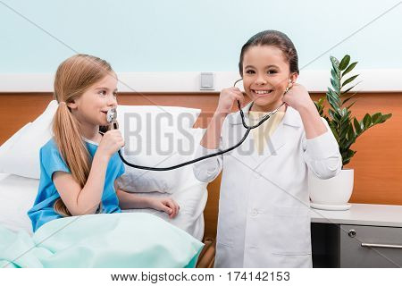 Smiling little girls playing doctor and patient with stethoscope in hospital