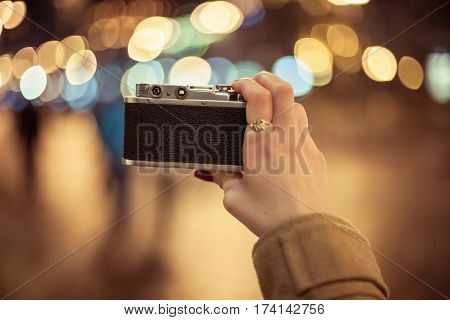 Hipster girl holding retro camera taking photos of night city, point of view shot