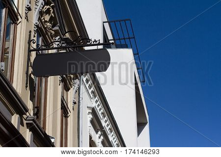 Horizontal front view of empty black square vintage signage on a white building with classical architecture hanging with chains
