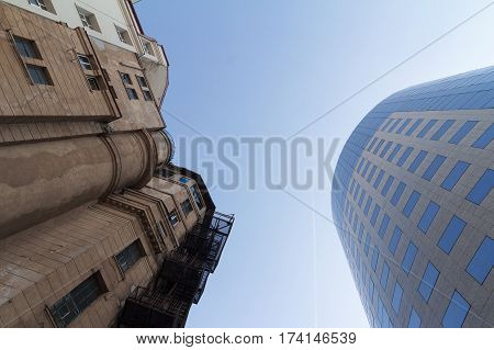 Side by side photo of classical building in front of modern glass office building with blue sky in between