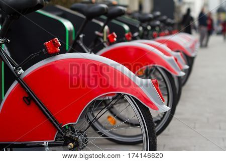 horizontal perspective view of city bike stand with row of red bicycles for rent on a city street and people in the background selective focus