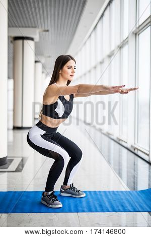 Deep squat. Side view of beautiful woman in sportswear doing squat and holding dumbbells while standing in front of window at gym