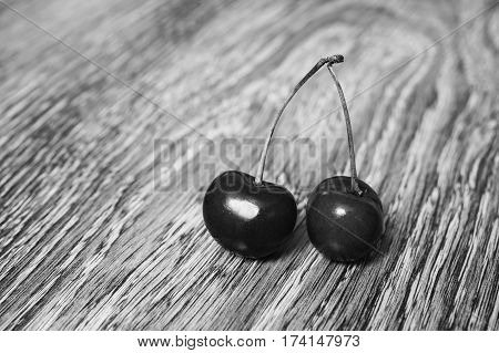 Black and white art photography monochrome ripe juicy cherry on wooden background. Word love laid out cherries. Ripe summer fruit.