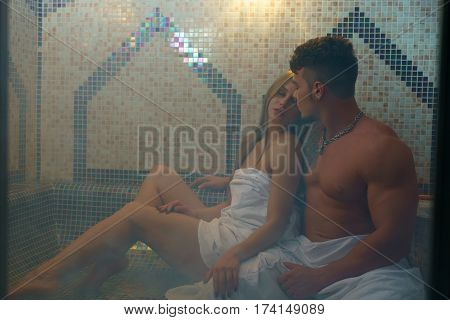 Gorgeous longhaired young blonde wrapped in white towel and her sexy athletic lover posing in hamam