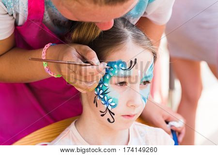 Face art for little girl. Blue butterfly painting. Children birthday party entertainment, artist making funny makeup