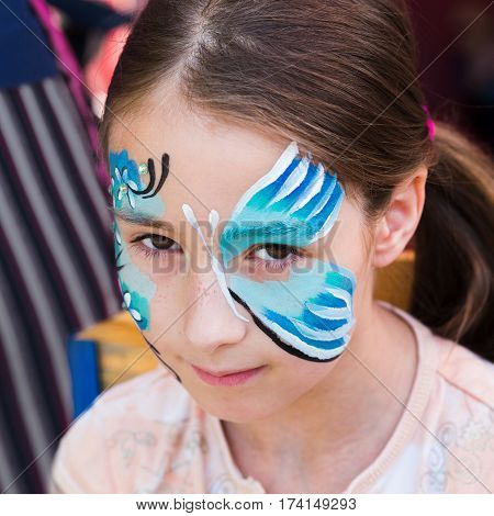 Small girl portrait with funny face art painting. Child with blue butterfly drawing. Children event, birthday party and modern creative entertainment.