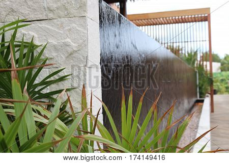 Waterfall cascading over black tiled wall with palms.