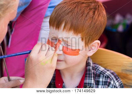 Child animator, artist's hand draws face art painting to little funny boy. Painter makes tiger eyes on kid. Children holiday, event, birthday party, entertainment.