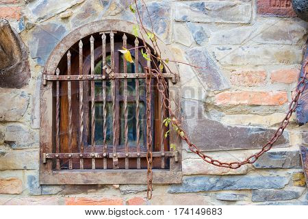 Old window with bars. Old window with bars. Stone wall and iron though