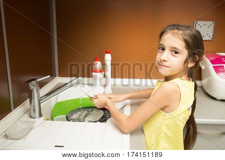 little girl makes dishes cleaning using water and sponge shot in household environment