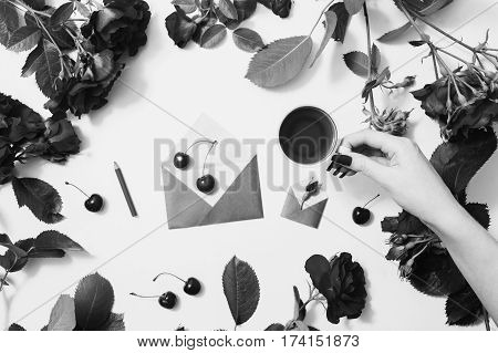 Black and white art photography monochrome female hand with red fingernails holding a cup of tea ripe cherries small envelopes roses lay on a white background. Berry compote. Flat lay