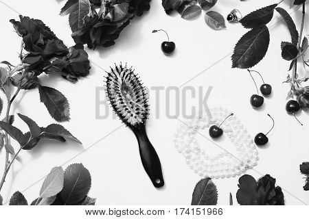 Black and white art photography monochrome fountain pen hairbrush lipstick ring ripe cherries small envelopes roses with leaves lay on white background. Flat lay. Flower frame. Female boudoir
