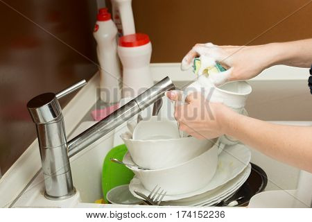 close up hands of Woman Washing Dishes in the kitchen