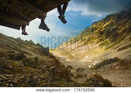 People sit on a wooden flooring above the mountain valley near the glacier under Mt.Titnuld. Caucasian Mountains Georgia region Svanetia.