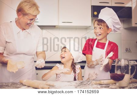 Grandmother with grandchildren baking cookies prepare dough