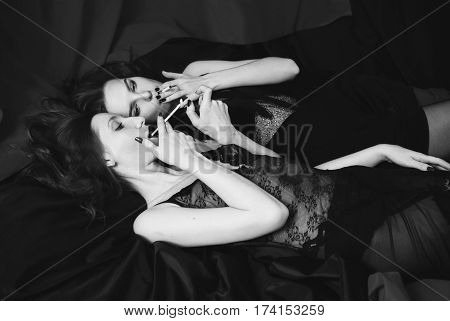 Black and white art photography monochrome two girl hugging and smoke on black background. Two lesbian women. Long hair. Beautiful sexy lingerie transparent. Love between girls. Bad habit