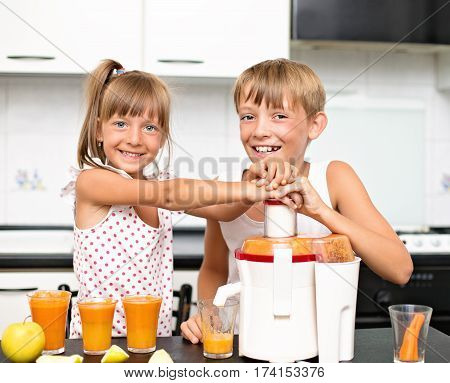 cute kids making carrot and apple juice with a juice extractor