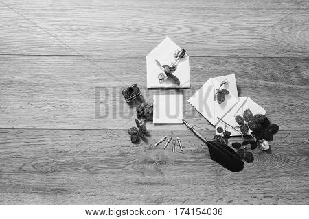 Black and white art photography monochrome fountain pen and ink on wooden background. White envelope and roses. Greeting card. Conceptual photography. Valentine day. Tips to pen. Flat lay copyspace