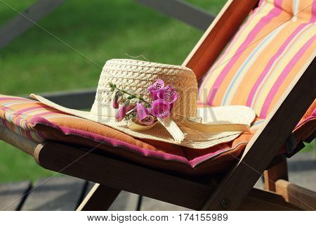 wooden chair with women hat outdoor in summer
