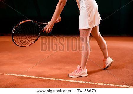 Legs of female tennis player on tennis court. Indoor tennis court