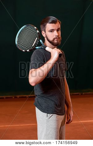 Handsome young man in t-shirt with racket on indoor tennis court