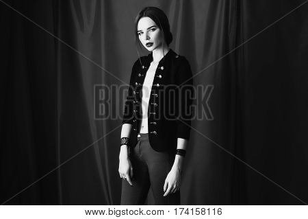 Black and white art photography monochrome beautiful girl in black unbuttoned jacket with red lips on dark background looking at the camera. Fashion black white photography. Bright appearance. Black white concept