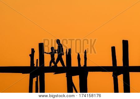 silhouette of tourist father and son crossing the river on the longest bridge in the world, U-Bein Bridge, Mandalay, Myanmar.