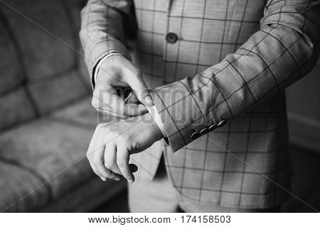 Black and white art photography monochrome man buttoning his waistcoat on. Men's style. Professions. Preparing to work on an appointment. Gray waistcoat