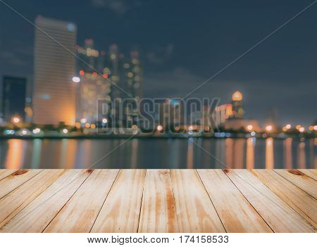 Empty wooden table top with blurred city skyline background at night can be used for montage or display your products