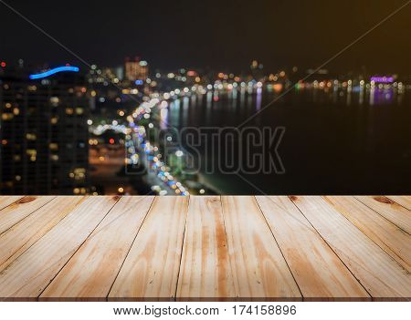 Empty brown wooden table top with blurred aerial city skyline background at night can be used for montage or display your products