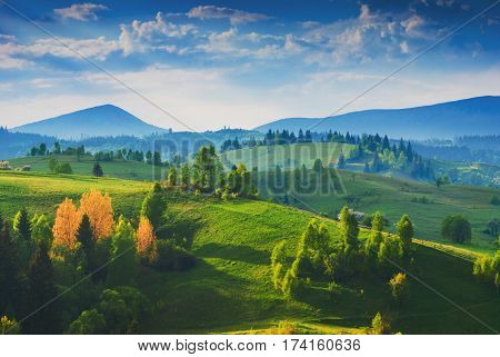 Colorful spring sunrise in the Carpathian misty village with green hills and valleys in golden morning light